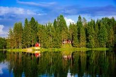 夏天村庄或原木小屋由蓝色湖在农村芬兰 免版税库存照片