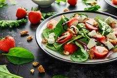 夏天果子草莓,菠菜沙拉用核桃,希腊白软干酪香醋,无头甘蓝 在板材 概念健康食品 库存图片