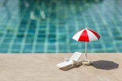 夏天概念背景、海滩睡椅和伞在游泳池 免版税图库摄影