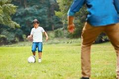 夏天橄榄球 踢足球的爸爸和儿子 图库摄影