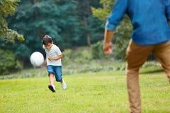 夏天橄榄球 踢足球的爸爸和儿子 库存图片