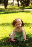 夏天浅绿色的礼服的逗人喜爱的矮小的一个岁女孩得到接触在草坪的草喜悦  免版税库存图片