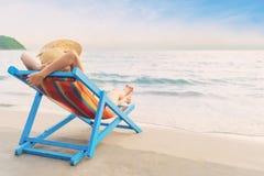 夏天海滩假期概念、亚洲妇女有放松和胳膊在椅子海滩在酸值Mak,传统,泰国的帽子的 免版税库存图片