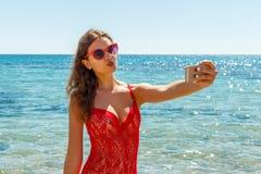 夏天海滩拍乐趣与智能手机的假期女孩流动selfie照片 戴红色太阳镜的女孩摆在为selfie 图库摄影