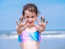 夏天海滩-女孩有美好时光手段海滩 使用在沙滩的孩子 在手上的焦点 库存图片