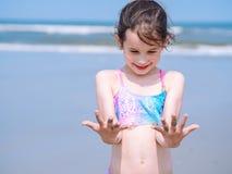 夏天海滩-女孩有美好时光手段海滩 使用在沙滩的孩子 在手上的焦点 图库摄影