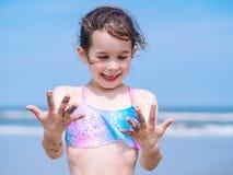 夏天海滩-女孩有美好时光手段海滩 使用在沙滩的孩子 在手上的焦点 库存照片