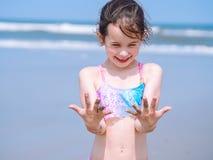 夏天海滩-女孩有美好时光手段海滩 使用在沙滩的孩子 在手上的焦点 免版税库存图片