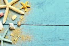夏天海背景 海星、贝壳和沙子在木蓝色背景 免版税图库摄影