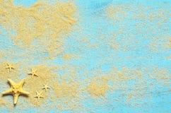 夏天海背景 海星和沙子在木蓝色背景 库存图片