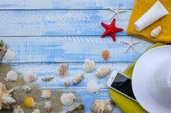 夏天海滩海概念 用不同的辅助部件,壳,海星,毛巾,遮光剂,沙子的蓝色木背景 免版税图库摄影