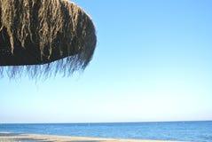 夏天海滩背景,与遮阳伞和蓝天 免版税库存图片