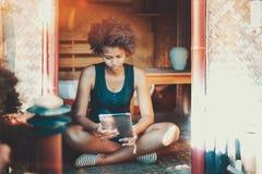 夏天游廊的蓬松卷发女孩与片剂个人计算机 免版税库存图片