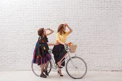 夏天礼服的两名愉快的妇女在一辆减速火箭的自行车一起乘坐 免版税库存照片