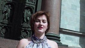 夏天礼服的俏丽的女孩唱歌在老orthodoxal教会门前面的 影视素材