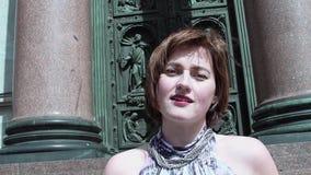 夏天礼服的俏丽的妇女唱歌在老orthodoxal教会门前面的 影视素材