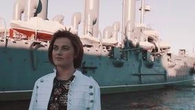 夏天礼服的可爱的少妇微笑在老战舰博物馆前面的 影视素材