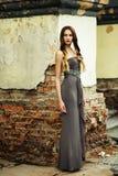 夏天礼服的妇女对老石墙, 库存图片