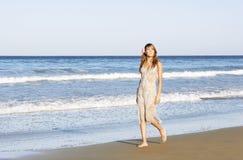 夏天礼服的妇女走横跨海滩的 免版税图库摄影