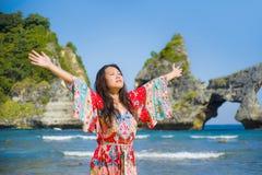 夏天礼服的年轻愉快和俏丽的旅游亚裔韩国妇女享受热带天堂海滩假日的摆在胳膊打开了fre 免版税图库摄影