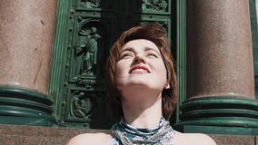 夏天礼服的快乐的女孩微笑在老orthodoxal教会门前面的 股票视频