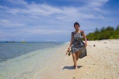 夏天礼服的愉快的亚裔中国妇女走在美丽的泰国海岛海滩的在蓝天下在假日 库存照片