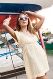 夏天礼服的美丽的女孩在海码头 免版税库存图片