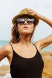 黑夏天礼服的逗人喜爱的女孩在大石头 免版税图库摄影