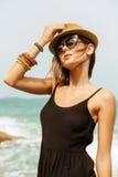 黑夏天礼服的逗人喜爱的女孩在大石头 免版税库存图片