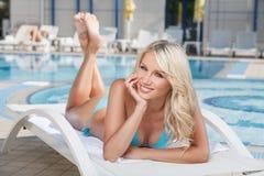 夏天秀丽。说谎在甲板的比基尼泳装的快乐的少妇 免版税库存照片