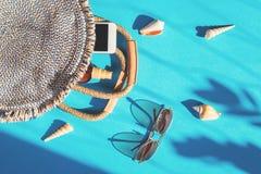 夏天秸杆袋子和太阳镜在蓝色背景 免版税库存照片