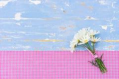 夏天美丽的花束开花在浅兰的木头的延命菊雏菊与桃红色被检查的织品和拷贝空间 库存照片