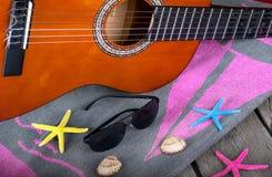 夏天背景海滩酒吧声学吉他星帽子和海星在木头 免版税库存照片
