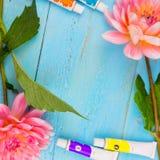 夏天背景 大丽花、油漆、刷子和一块帆布在蓝色木背景 艺术 文本的空间 免版税库存图片