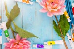 夏天背景 大丽花、油漆、刷子和一块帆布在蓝色木背景 艺术 文本的空间 库存图片