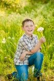 夏天自然的男孩用蒲公英 免版税库存图片
