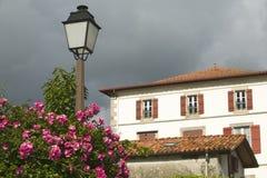 夏天花、灯岗位和家在Sare,法国在巴斯克地区西班牙法国边界的,一个小山顶17世纪村庄t的 免版税库存图片