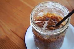 夏天茶点喝,在木桌安置的杯与在白色板材安置的拷贝空间的被冰的咖啡和两个 库存照片