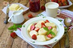夏天莓果早餐甜懒惰pierogi、饺子与酸性稀奶油,黄油和草莓在木背景 意大利gnocchi 库存照片