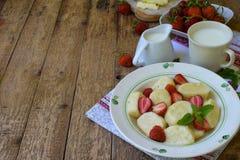 夏天莓果早餐甜懒惰pierogi、饺子与酸性稀奶油,黄油和草莓在木背景 意大利gnocchi 免版税库存照片