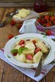 夏天莓果早餐甜懒惰pierogi、饺子与酸性稀奶油,黄油和草莓在木背景 意大利gnocchi 免版税库存图片