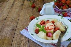 夏天莓果早餐甜懒惰pierogi、饺子与酸性稀奶油,黄油和草莓在木背景 意大利gnocchi 图库摄影