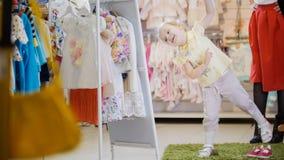 夏天衣服的小女孩获得在镜子前面的乐趣在儿童` s服装店 库存照片