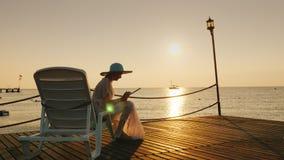夏天衣裳的一名妇女坐在码头的一个懒人 使用一种片剂 在海的美好的黎明,距离的是 图库摄影