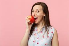 夏天衣裳的俏丽的年轻女人拿着在桃红色淡色墙壁背景的咬住的新鲜的成熟红色苹果果子 库存图片