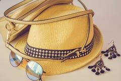 夏天辅助部件、袋子、草帽、太阳镜和耳环在桌上说谎 米黄颜色四个辅助部件,特写镜头 免版税库存照片