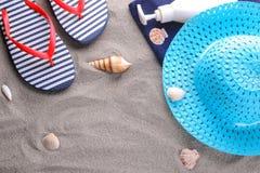 夏天辅助部件 啪嗒啪嗒的响声、一块毛巾和一个帽子在海的沙子 免版税库存照片