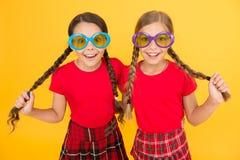 夏天辅助部件 女孩逗人喜爱的姐妹相似的成套装备戴夏季的五颜六色的太阳镜 时兴的孩子 免版税库存照片