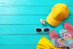 夏天辅助部件 盖帽、太阳镜、触发器、壳和桔子在蓝色木背景 顶视图和拷贝空间 图库摄影