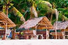 夏天遮光罩和竹扶手椅子在热带白色沙子靠岸 图库摄影